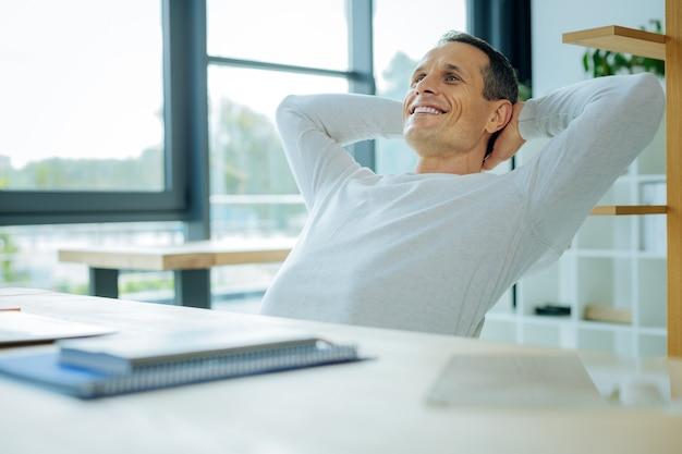Mogę odpocząć. miły, wesoły, pozytywny człowiek kończący swój projekt i czujący się szczęśliwy mając okazję do relaksu