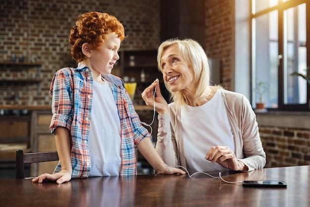 Mogę spróbować. pozytywnie nastawiona starsza kobieta uśmiecha się do swojego małego wnuka, jednocześnie spędzając razem czas i słuchając muzyki w domu.