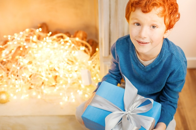 Mogę to teraz otworzyć. widok z góry na zdumionego rudego chłopca siedzącego obok ozdobnego kominka i trzymającego prezent na boże narodzenie.
