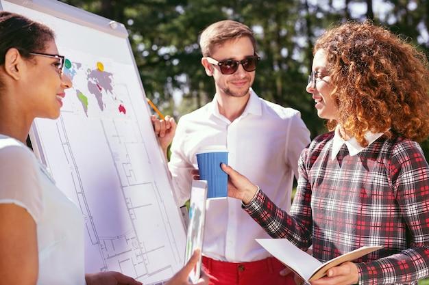 Moi najlepsi przyjaciele. uśmiechnięta dziewczyna z kręconymi włosami trzymająca kawę i rozmawiająca z przyjaciółmi o projekcie