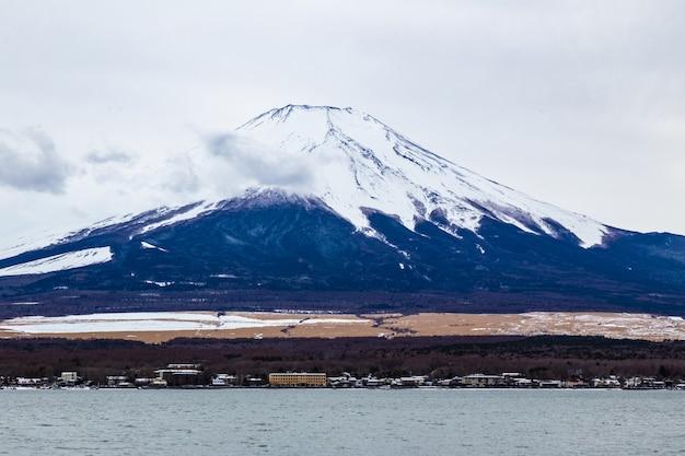 Moiunt fuji stoi wysoko na tle zachmurzonego białego nieba z kilkoma puszystymi chmurami unoszącymi się z przodu
