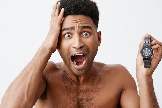 Mój autobus jest już w innym mieście. młody przystojny atrakcyjny ciemnoskóry mężczyzna z fryzurą afro obudził się późno i spóźnił się na pociąg do innego miasta. negatywne emocje