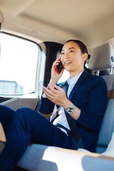 Mój biznes. pozytywna inteligentna bizneswoman mówi o pracy siedząc w swoim samochodzie
