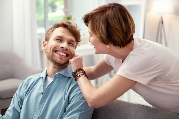 Mój chłopak. miła, miła kobieta dotykająca policzka syna, okazując jednocześnie swoje uczucia