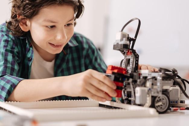 Mój cyfrowy przyjaciel. wprawny wesoły uroczy chłopiec siedzący w klasie, wyrażający radość i konstruujący robota
