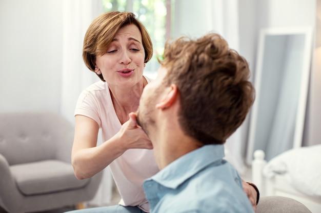 Mój drogi. radosna miła kobieta spędzająca czas z synem będąc w domu
