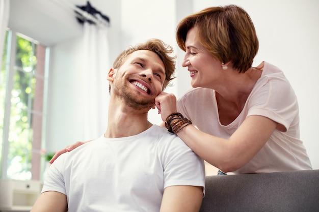 Mój drogi synu. radosna miła kobieta patrzy na syna, jednocześnie okazując mu miłość