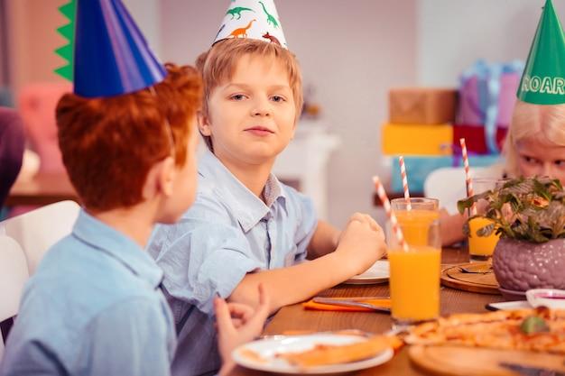 Mój dzień. uważny rudowłosy dzieciak siedzący w półpozycji i utrzymujący uśmiech na twarzy