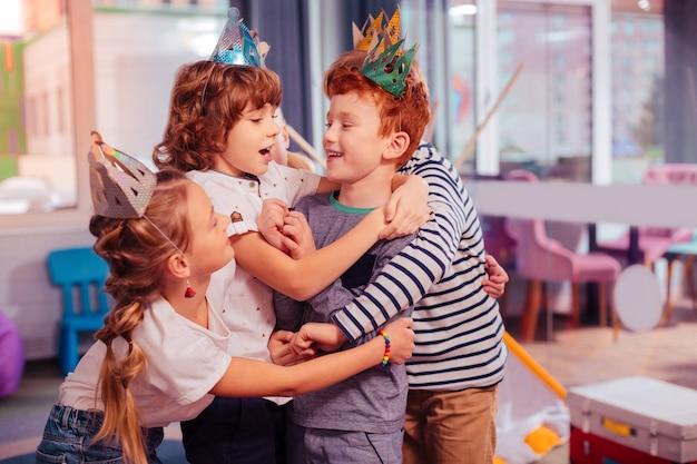 Mój kuzyn. wesoły rudowłosy dzieciak obejmujący swojego przyjaciela, śmiejąc się z żartu
