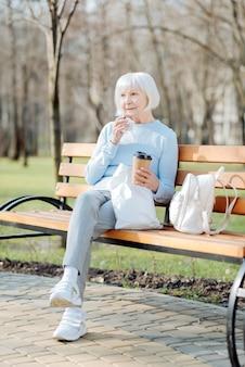 Mój lunch. zaalarmowana stara kobieta siedząca na ławce przy kawie i ciasteczku