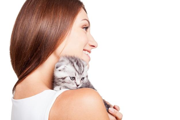 Mój mały futrzany przyjaciel. piękna młoda kobieta niesie swojego małego kotka na ramieniu i uśmiecha się stojąc na białym tle