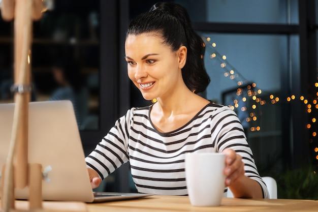 Mój napój. wesoła, przyjemna młoda kobieta, stawiając filiżankę na stole i uśmiechając się, patrząc na ekran laptopa