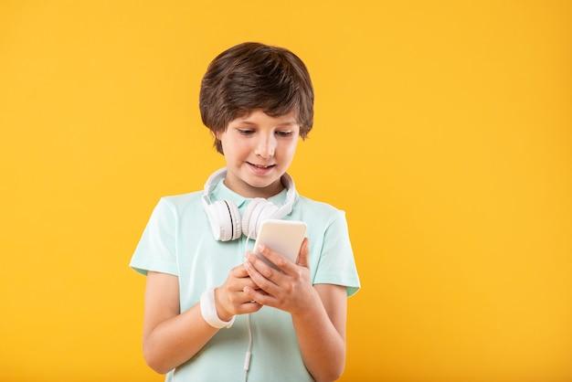 Mój nowy gadżet. zainspirowany ciemnowłosy uczeń korzystający z telefonu i noszący słuchawki
