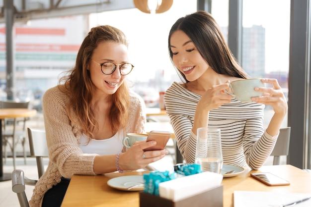 Mój nowy profil. śliczna, młoda rudowłosa kobieta pokazuje informacje na swoim smartfonie swojej najlepszej przyjaciółce podczas spotkania w kawiarni.