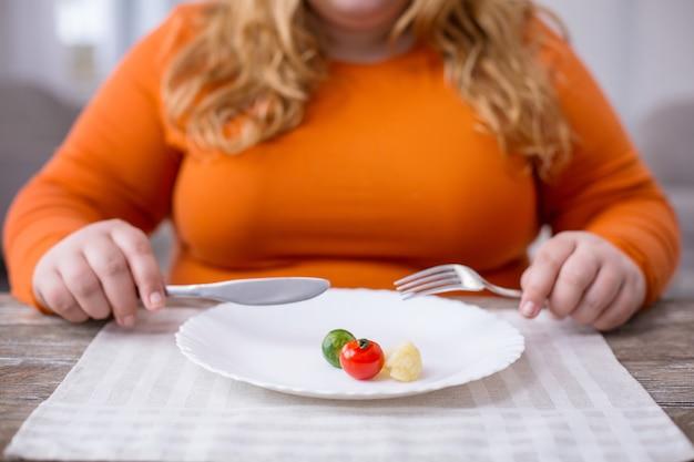 Mój nowy styl życia. młoda pulchna kobieta siedzi przy stole i zdrowo się odżywia