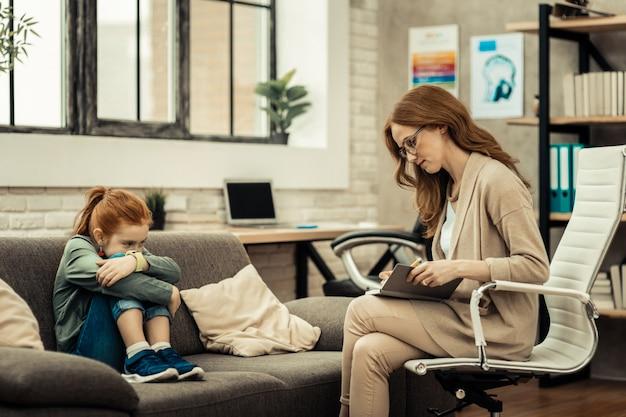 Mój pacjent. poważna inteligentna kobieta czyta swoje notatki podczas sesji z pacjentem