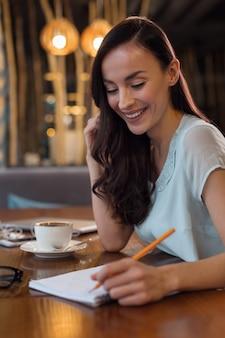 Mój pamiętnik. zamyślona, radosna, dobrze wyglądająca kobieta, uśmiechnięta, patrząc w dół i używając ołówka