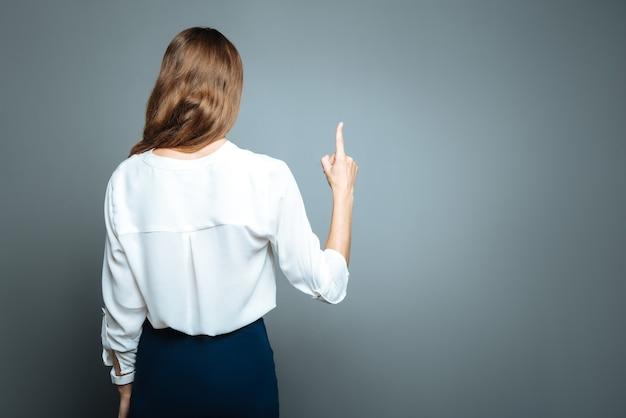 Mój pomysł. mądra, inteligentna młoda kobieta odwraca się do ciebie tyłem i wskazuje palcem wskazującym, mając pewien pomysł