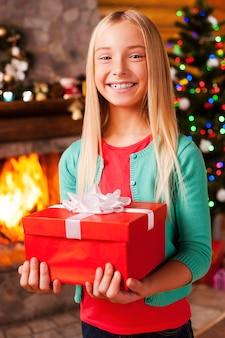 Mój prezent świąteczny! śliczna mała dziewczynka trzymająca pudełko z prezentami i uśmiechająca się z choinką i kominkiem w tle
