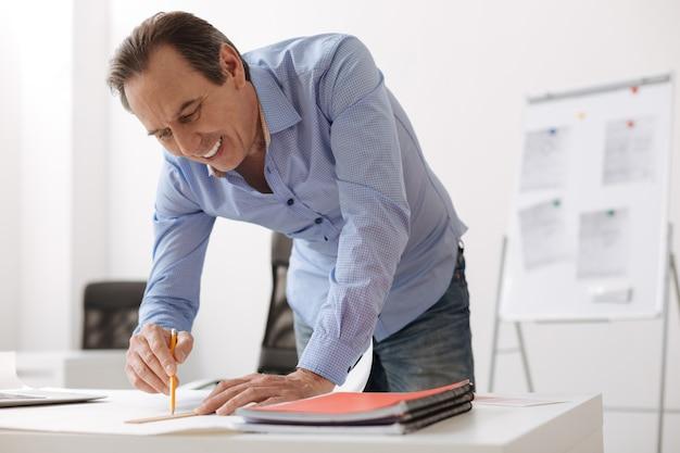 Mój projekt. dojrzały, pozytywnie nastawiony inżynier, stojący przy stole i rysujący plan podczas pracy