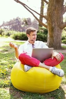 Mój relaks. szczęśliwy, dobrze zbudowany mężczyzna siedzi na świeżym powietrzu i pracuje na swoim laptopie