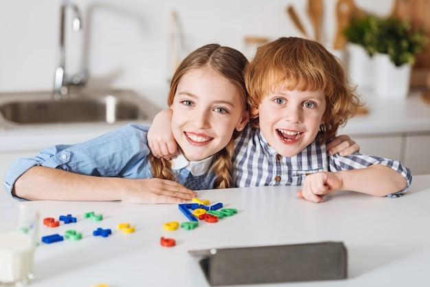 Mój ulubiony partner w grze. urocze, ciekawe i energiczne rodzeństwo spędzające weekendowy poranek w domu, grając w gry edukacyjne, jednocześnie pracując nad samokształceniem