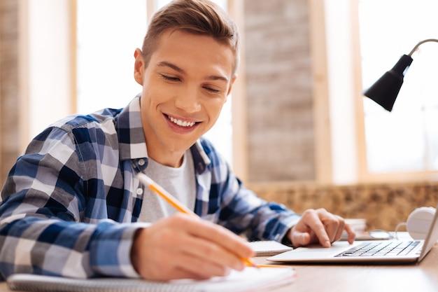 Mój ulubiony przedmiot. przystojny uśmiechnięty jasnowłosy chłopak pracuje na swoim laptopie i pisze w swoim notesie, siedząc przy stole