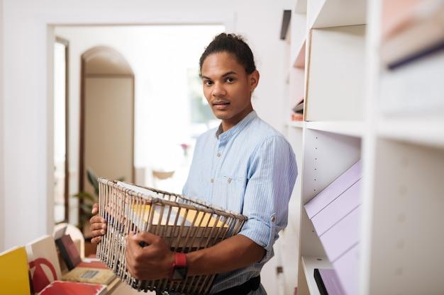 Mój wybór. zachwycony młody mężczyzna trzymający kosz podczas pracy w księgarni