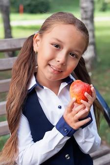 Mój zabawny przyjaciel. powrót do szkoły. mała dziewczynka z jabłkiem na świeżym powietrzu. odróbcie razem pracę domową. zdrowe i szczęśliwe dzieciństwo. 1 września
