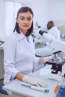 Mój zawód. zdeterminowana inteligentna naukowiec pracująca z mikroskopem i ubrana w mundur