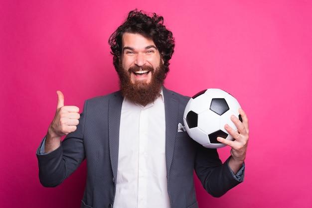 Mój zespół jest najlepszy, zdumiony brodaty mężczyzna w garniturze pokazujący kciuk do góry i trzymający piłkę nożną