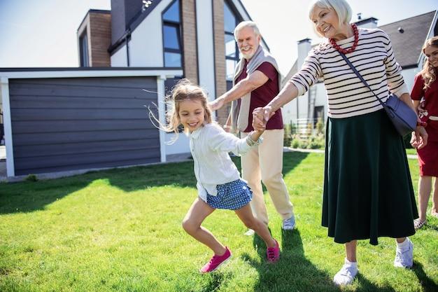 Moja babcia. szczęśliwa dojrzała kobieta patrząc na wnuczkę i ciesząc się przyjazną atmosferą