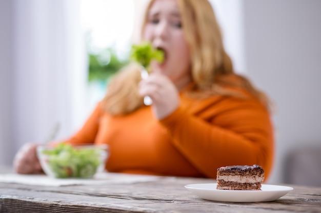 Moja dieta. nieszczęśliwa tęga kobieta, patrząc na deser i jedząc zdrowe śniadanie
