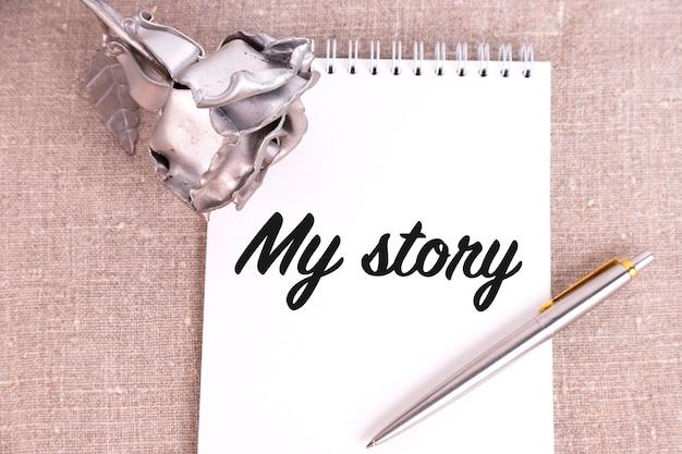 Moja historia, tekst jest zapisany w notatniku leżącym na lnianym lnie i żelaznym kwiatku róży.