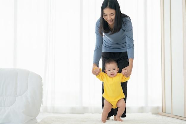 Moja mała dziewczynka stawia pierwsze kroki. rodzina szczęśliwe małe dziecko uczy się chodzić z pomocą matki w domu