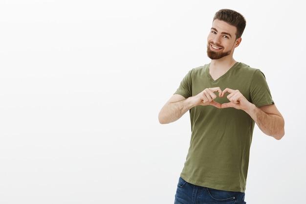 Moja miłość jest twoja. portret czarującego charyzmatycznego chłopaka rasy kaukaskiej z brodą w koszulce, uśmiechając się szeroko, pokazując gest serca