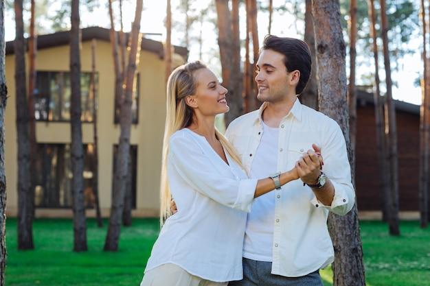 Moja miłość. radosna pozytywna kobieta patrząc na męża stojąc razem z nim