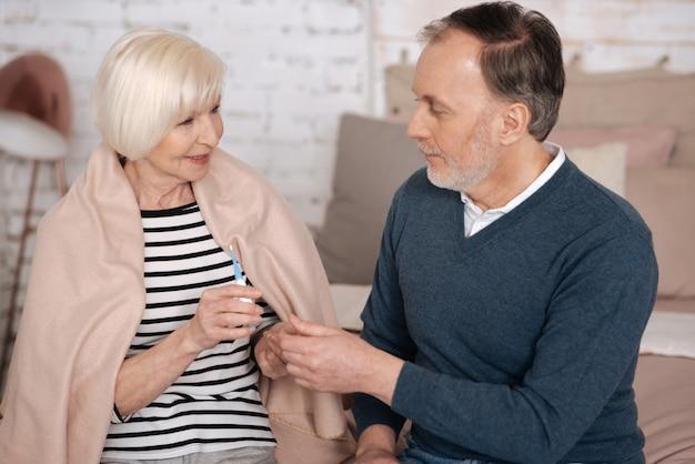 Moja miłość. starszy mężczyzna jest mężczyzną, który dba o swoją chory żonę, pokrytą kocem i trzymając termometr.