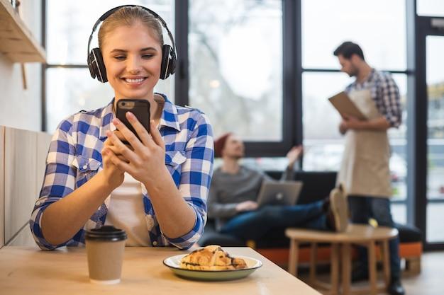 Moja muzyka. radosna piękna miła kobieta siedzi przy stole i słucha swojej ulubionej piosenki, jednocześnie ciesząc się muzyką