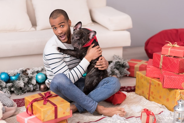 Moja najlepsza przyjaciółka. przyjemnie wyglądający brodacz siedzi pośród prezentów bożonarodzeniowych i trzyma psa, bawiąc się świetnie