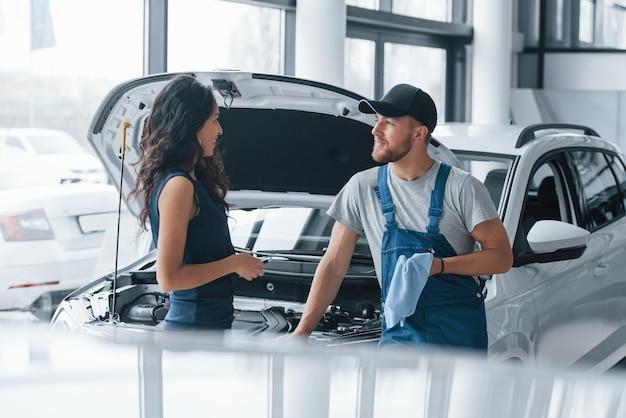 Moja praca jest skończona. kobieta w salonie samochodowym z pracownikiem w niebieskim mundurze zabierająca naprawiony samochód z powrotem.