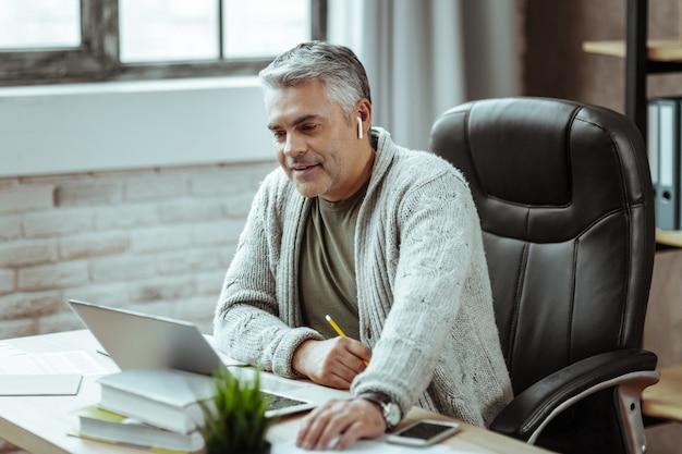 Moja praca. miły, inteligentny biznesmen siedzi w swoim biurze, ciesząc się swoją pracą