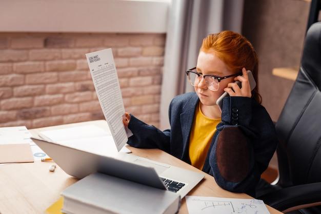 Moja przyszła praca. inteligentna rudowłosa dziewczyna rozmawia przez telefon trzymając dokument w dłoni