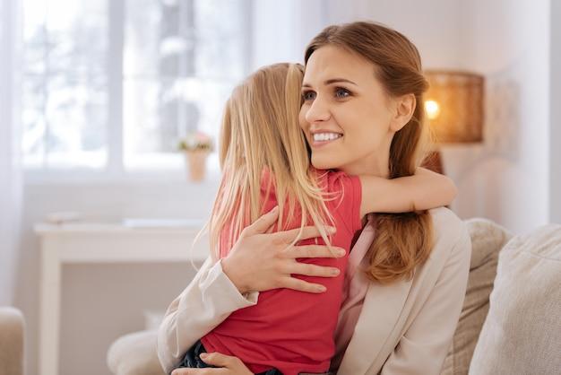 Moja ukochana córko. szczęśliwa zachwycona miła mama uśmiechająca się i przytulająca córkę, jednocześnie wyrażając jej swoje uczucia