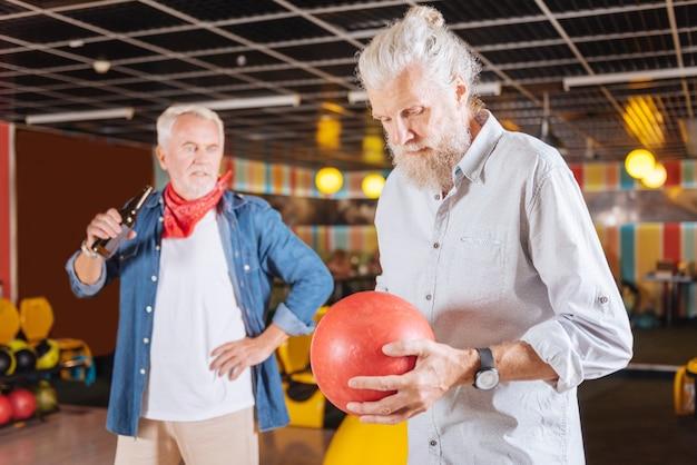 Moja ulubiona gra. miły starszy mężczyzna patrząc na kulę do kręgli, trzymając go w ręku
