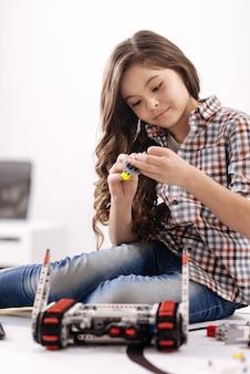 Moja ulubiona gra. zdolna, urocza dziewczynka siedząca w laboratorium robotyki i trzymająca szczegóły cyber-robota, wyrażająca zainteresowanie
