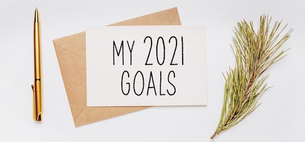 Moje cele na 2021 rok z kopertą, gałązką świerku i złotym piórem na białym tle. wesołych świąt i nowego roku koncepcja