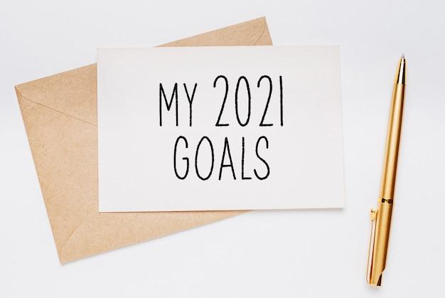 Moje cele na 2021 rok z kopertą i złotym długopisem na białej powierzchni