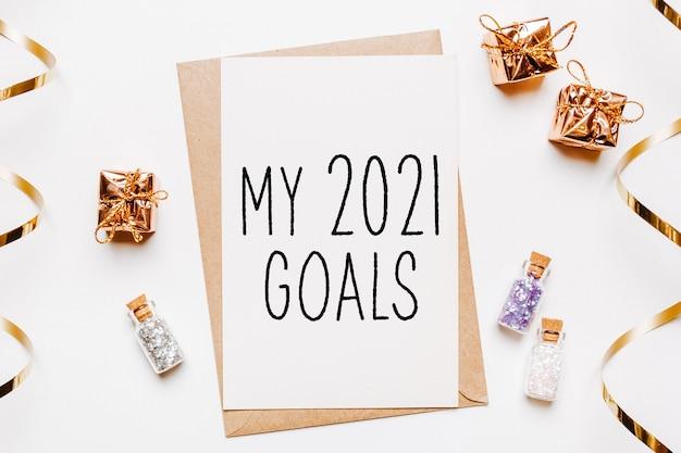 Moje cele na 2021 rok z kopertą, prezentami i złotymi brokatowymi gwiazdkami na białym tle