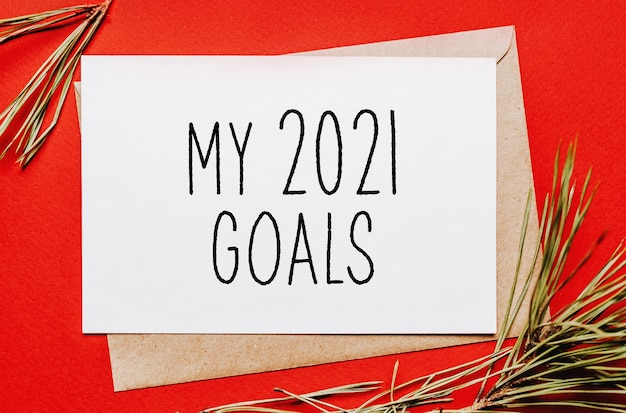 Moje cele na rok 2021 boże narodzenie z gałąź jodła na czerwonym tle na białym tle. koncepcja nowego roku